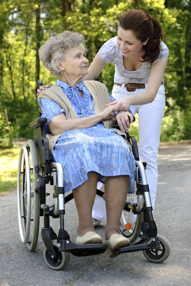 woman helping elderly woman in wheelchair