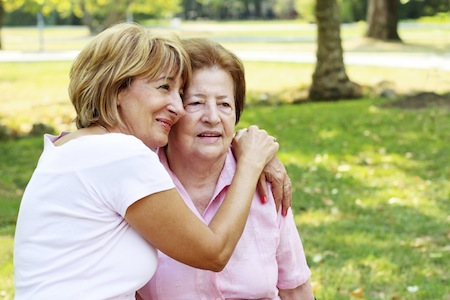 Beautiful mature woman embracing her senior mother in the park.
