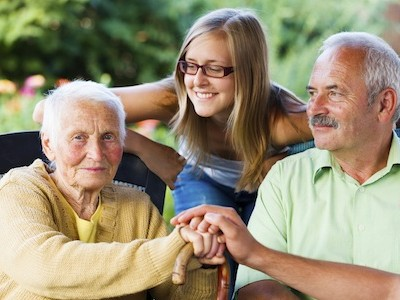 Elderly woman welcoming her family - son and granddaughter in the garden of the nursing home.