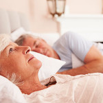 elderly woman laying awake in bed with her husband sleeping next to her