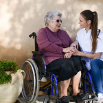 older woman in wheelchair receiving elderly care from her caregiver