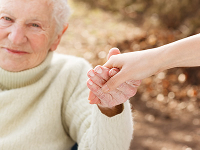 Elderly woman holding someone's hand